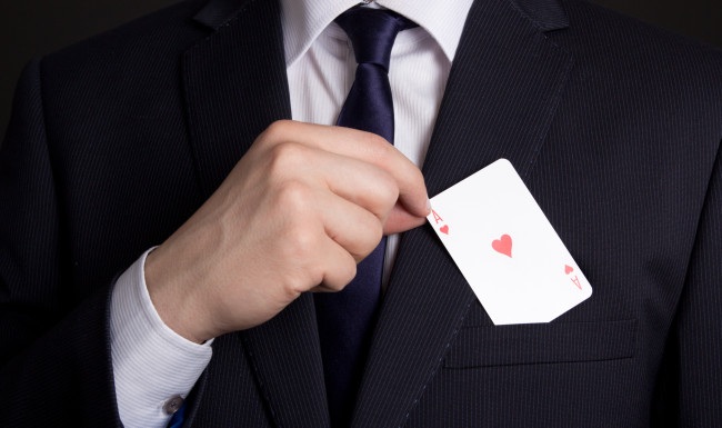mans hand hiding playing card in suit pocket